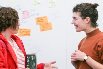 visiting speaker talks with talk attendee in front of wall with post-its