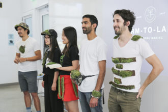 students demonstrate project wearing clothing items with plants growing on them